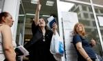 Una mujer saliendo de la  oficina del fondo estatal de salud en Atenas.  Los  pacientes dicen que han estado  yendo de farmacia en farmacia en busca de medicamentos recetados. F. John Kolesidis / Reuters
